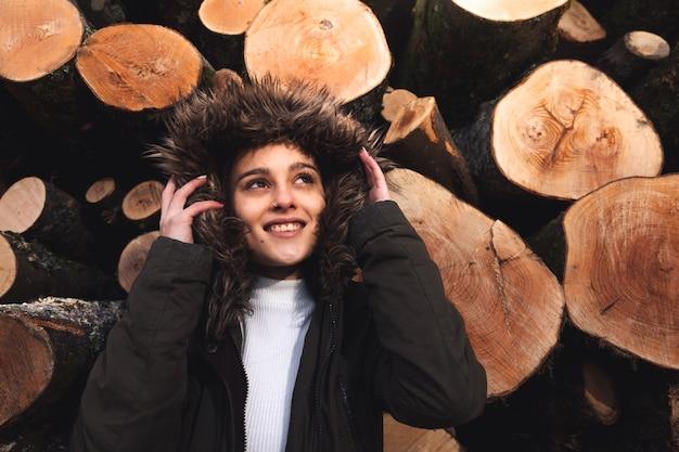 Mulher jovem em um dia frio atrás de troncos cortados.