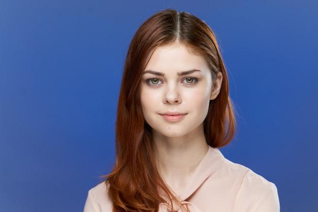 Mulher jovem em um fundo azul brilhante posando, emoções diferentes, maquete