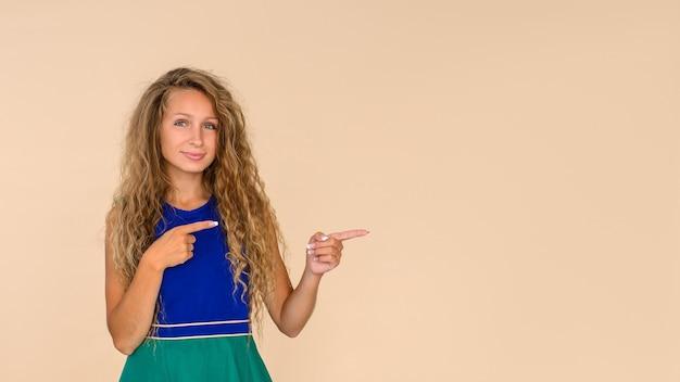 Mulher jovem em um fundo bege isolado aponta com os dedos para liberar espaço para uma inscrição