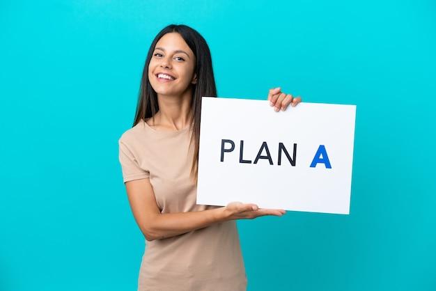 Mulher jovem em um fundo isolado segurando um cartaz com a mensagem plano a com expressão feliz