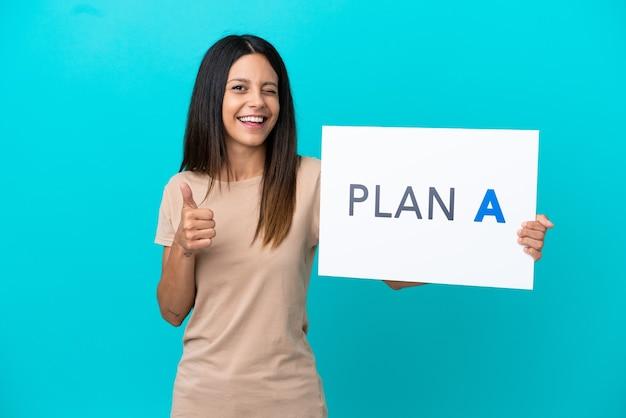Mulher jovem em um fundo isolado segurando um cartaz com a mensagem plano a e apontando para a frente