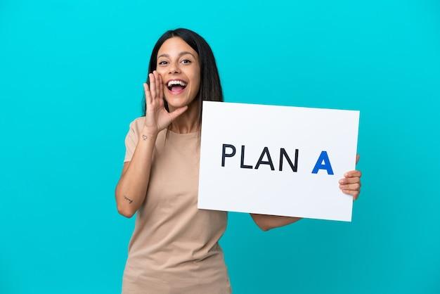 Mulher jovem em um fundo isolado segurando um cartaz com a mensagem plano a e gritando
