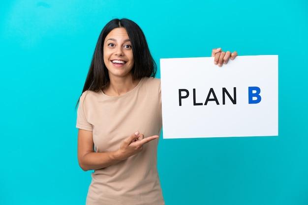 Mulher jovem em um fundo isolado segurando um cartaz com a mensagem plano b com expressão de surpresa