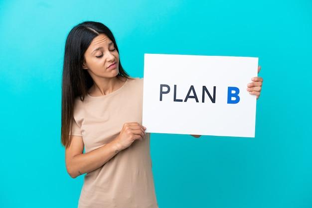 Mulher jovem em um fundo isolado segurando um cartaz com a mensagem plano b com expressão triste