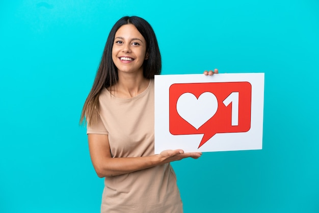 Mulher jovem em um fundo isolado segurando um cartaz com o ícone de semelhante com uma expressão feliz