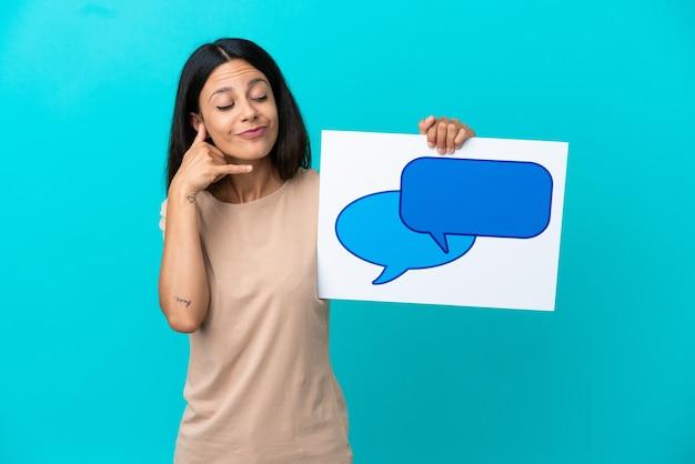 Mulher jovem em um fundo isolado segurando um cartaz com o ícone de um balão de fala e fazendo gestos de telefone