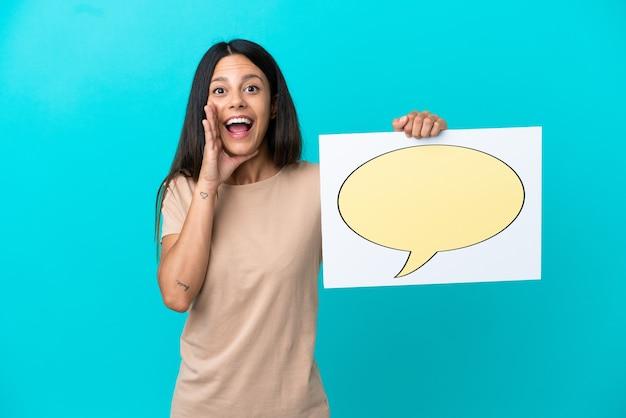 Mulher jovem em um fundo isolado segurando um cartaz com o ícone de um balão de fala e gritando