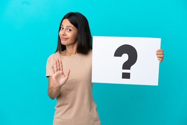 Mulher jovem em um fundo isolado segurando um cartaz com o símbolo do ponto de interrogação e fazendo o sinal de pare