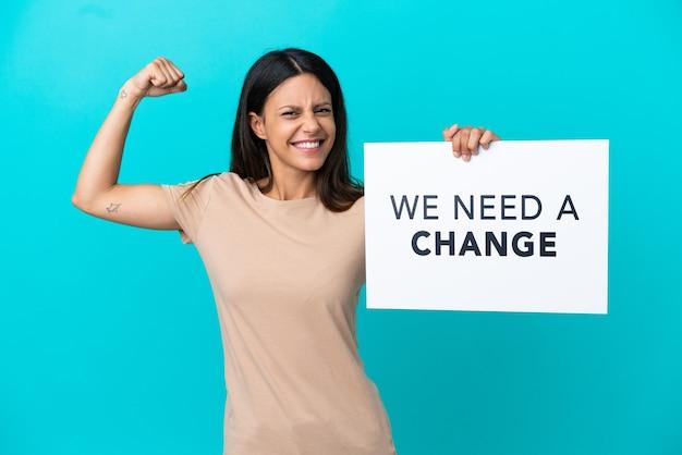 Mulher jovem em um fundo isolado segurando um cartaz com o texto precisamos de uma mudança e fazendo um gesto forte