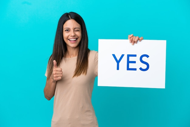 Mulher jovem em um fundo isolado segurando um cartaz com o texto sim e apontando para a frente