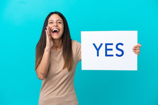 Mulher jovem em um fundo isolado segurando um cartaz com o texto sim e gritando