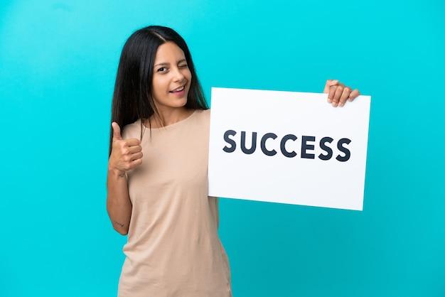 Mulher jovem em um fundo isolado segurando um cartaz com o texto sucesso e apontando para a frente