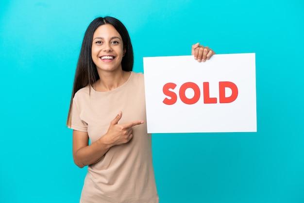 Mulher jovem em um fundo isolado segurando um cartaz com o texto vendido e apontando-o