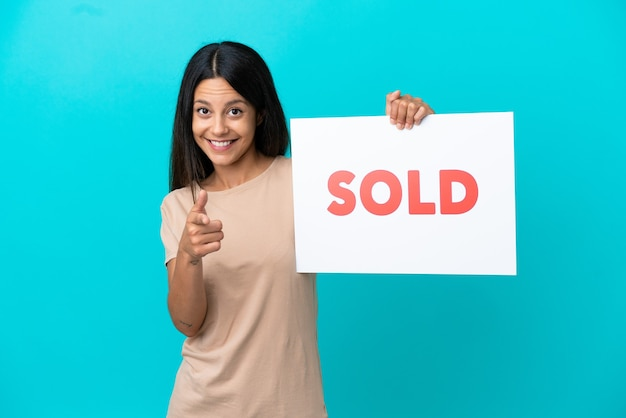 Mulher jovem em um fundo isolado segurando um cartaz com o texto vendido e apontando para a frente