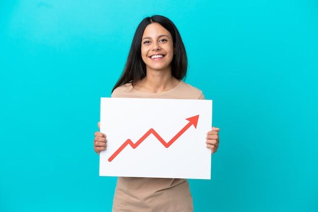 Mulher jovem em um fundo isolado segurando uma placa com um símbolo de seta de estatísticas crescentes e com uma expressão feliz