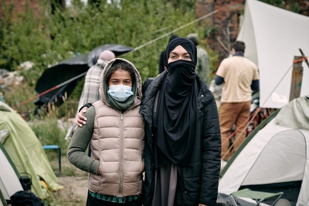 Mulher jovem em um hijab e sua filha em pé contra o acampamento
