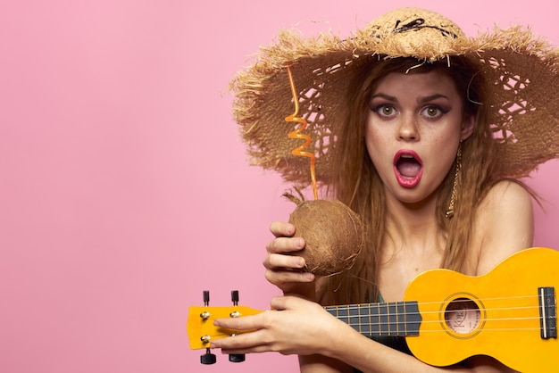 Mulher jovem em um maiô e um chapéu com abacaxi na mão, festa divertida, praia em casa tocando cavaquinho