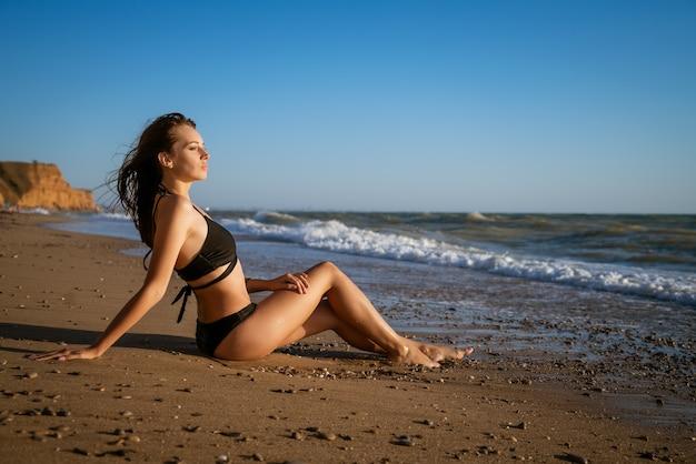 Mulher jovem em um maiô sentada à beira-mar ao pôr do sol