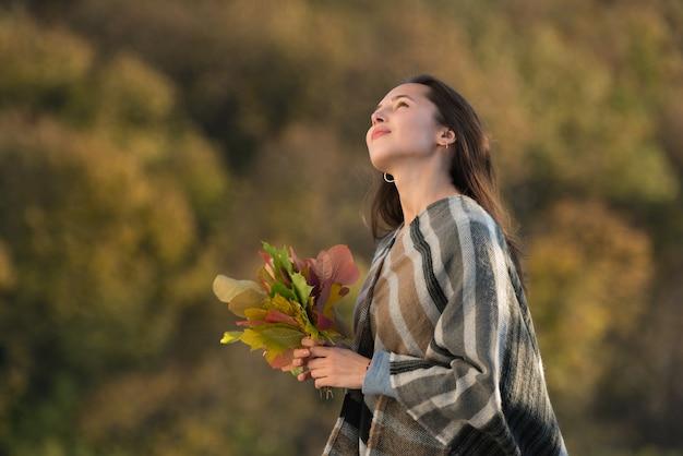 Mulher jovem em um poncho com um buquê de folhas de outono