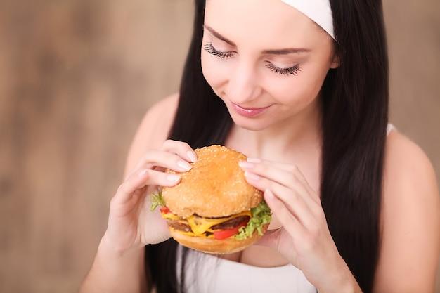 Mulher jovem em um restaurante requintado come um hambúrguer, ela se comporta de maneira inadequada