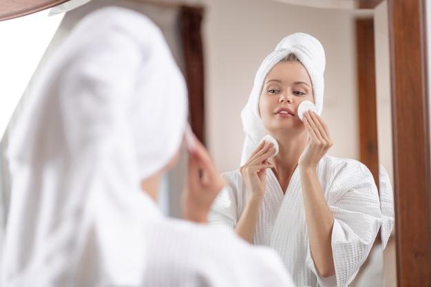 Mulher jovem em um roupão de banho branco com uma toalha na cabeça