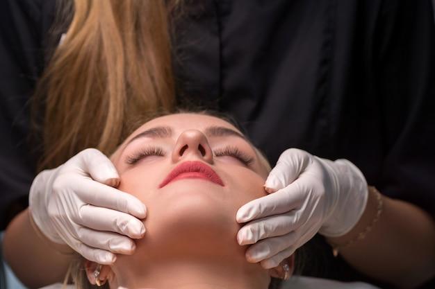 Mulher jovem em um salão de beleza. a esteticista faz um procedimento de limpeza facial. foco nos lábios