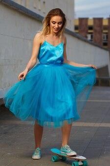 Mulher jovem em um skate de vestido azul em uma cidade