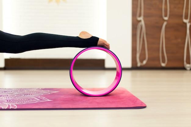 Mulher jovem, em, um, sportswear, ioga, exercícios, com, um, roda ioga, em, ginásio
