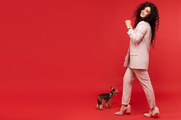 Mulher jovem em um terno bege da moda caminhando com um lindo yorkshire terrier