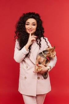 Mulher jovem em um terno bege da moda posando com um yorkshire terrier fofo