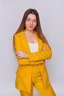 Mulher jovem em um terno de calça amarela e blusa branca cruzou os braços contra e olha para a câmera. espaço em branco.