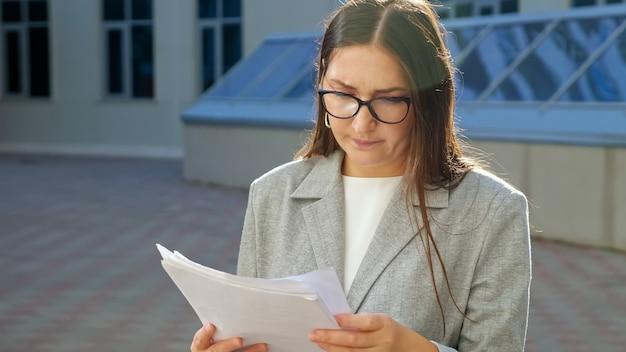 Mulher jovem em um terno formal e óculos com uma cara séria examina documentos na rua.