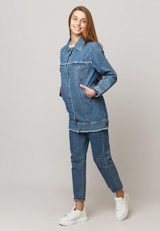 Mulher jovem em um terno jeans em um branco