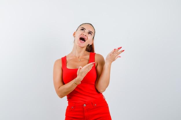 Mulher jovem em um top vermelho, calças fazendo gesto de pergunta, olhando para cima e parecendo curioso, vista frontal.