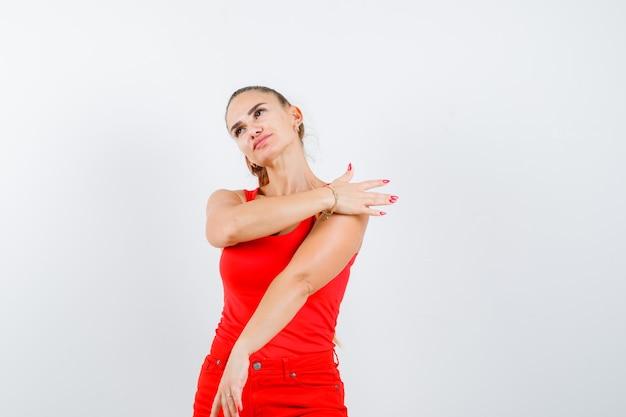 Mulher jovem em um top vermelho, calças segurando a palma da mão no ombro e olhando pensativa, vista frontal.