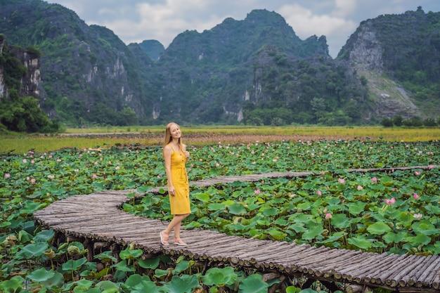 Mulher jovem em um vestido amarelo no caminho entre o lago de lótus mua caverna ninh binh vietnã vietnã