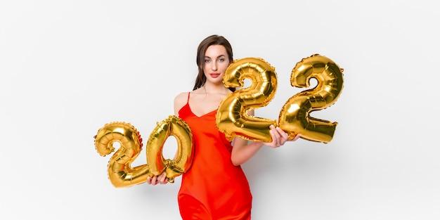 Mulher jovem em um vestido de cocktail vermelho com maquiagem brilhante, comemorando o ano novo e segurando um balão dourado.