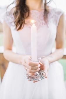 Mulher jovem em um vestido de noite segurando uma vela