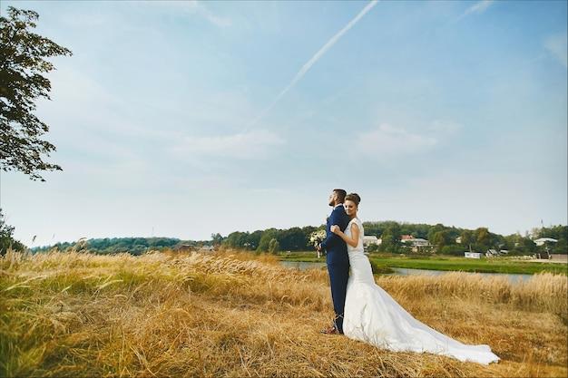 Mulher jovem em um vestido de noiva branco e um homem bonito e brutal em um terno azul posando ao ar livre
