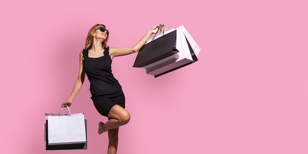Mulher jovem em um vestido preto e óculos escuros segurando sacolas de compras em um fundo rosa