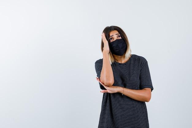 Mulher jovem em um vestido preto, máscara preta segurando uma mão na têmpora, a outra mão sob o cotovelo e parecendo aflita, vista frontal.