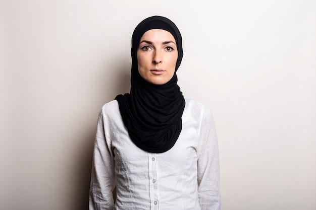 Mulher jovem em uma camisa branca e hijab