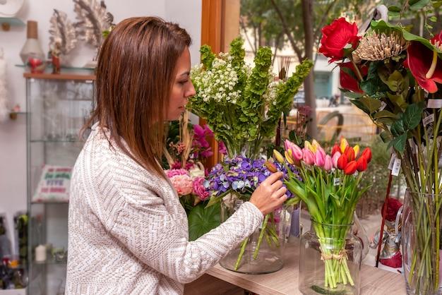 Mulher jovem em uma floricultura observando flores e tulipas