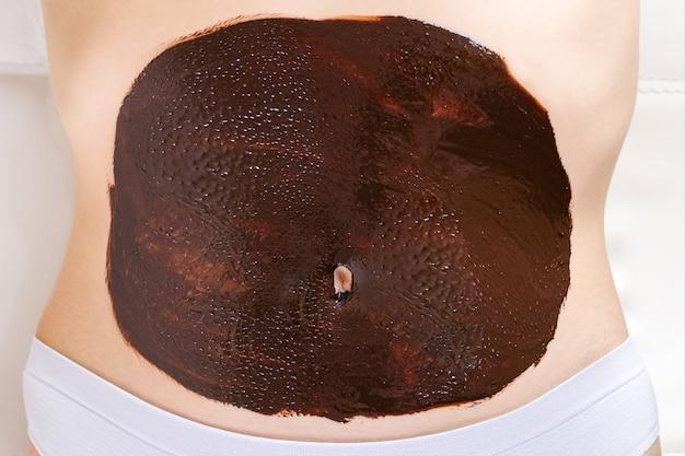 Mulher jovem em uma massagem de chocolate. envolvimento de barriga de chocolate
