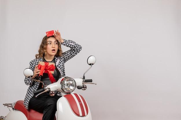 Mulher jovem em uma motocicleta segurando um cartão e um presente de frente