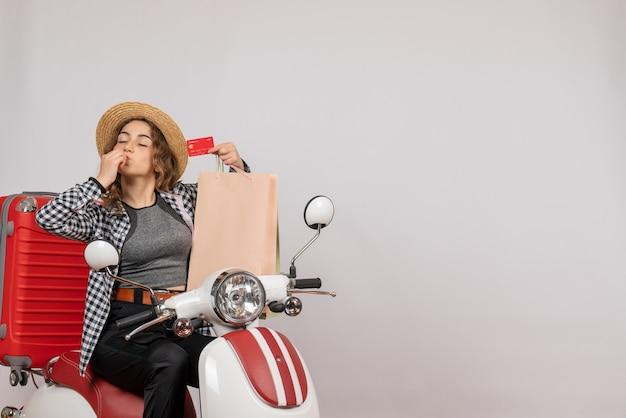 Mulher jovem em uma motocicleta segurando um cartão fazendo beijo de chef