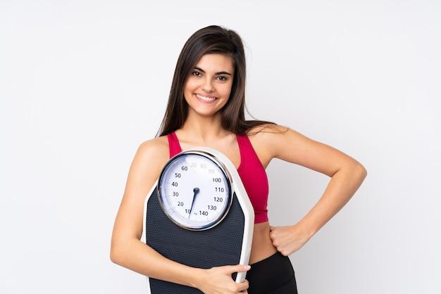 Mulher jovem em uma parede branca isolada com os braços na cintura e segurando uma balança