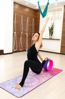 Mulher jovem em uma roupa esportiva exercícios de ioga com uma roda de ioga na academia