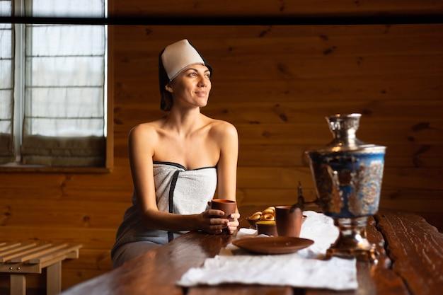 Mulher jovem em uma sauna com um boné na cabeça se senta a uma mesa e bebe chá de ervas, desfrutando de um dia de bem-estar