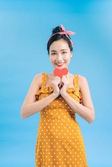 Mulher jovem em vestido casual posando com coração vermelho isolada em azul